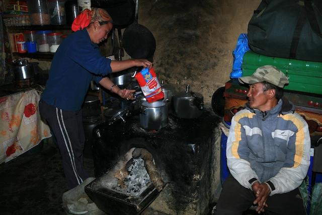 Es ist schon erstaunlich, was für ein vorzügliches Essen die Sherpafrauen auf ihrer einen Feuerstelle zubereiten können. Das Gemüse wird meist frisch hinter dem Haus geerntet, Reis und Kartoffeln werden sozusagen ständig stand by gehalten. Doch Zeit muß man trotzdem haben. Anderthalb Stunden braucht die Hausfrau manchmal schon, bis die Bestellung auf dem Tisch steht.